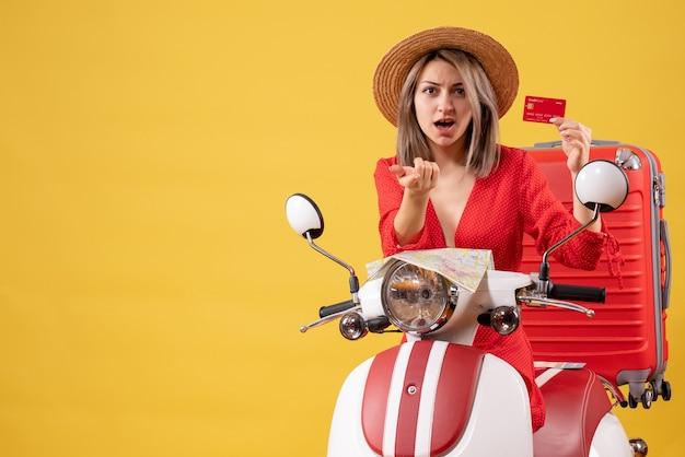 Vue de face jeune femme en robe rouge tenant une carte de crédit pointant vers près d'un cyclomoteur