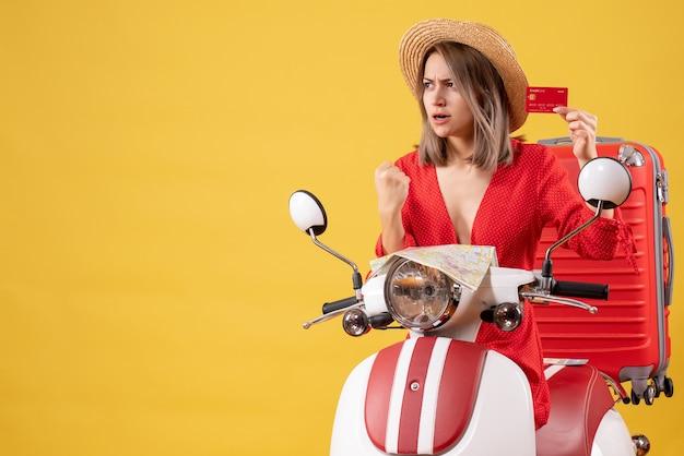 Vue de face jeune femme en robe rouge tenant une carte de crédit près d'un cyclomoteur