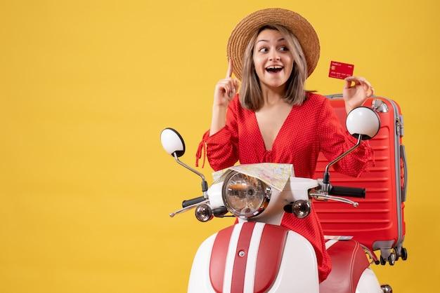 Vue de face de la jeune femme en robe rouge tenant une carte de crédit surprenante avec une idée près de cyclomoteur