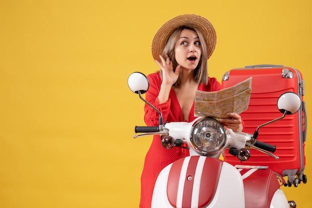 Vue de face jeune femme en robe rouge tenant une carte écoutant quelque chose près d'un cyclomoteur