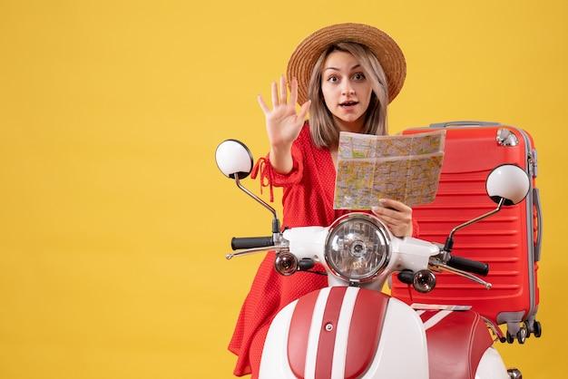 Vue de face jeune femme en robe rouge tenant une carte faisant un panneau d'arrêt debout près d'un cyclomoteur