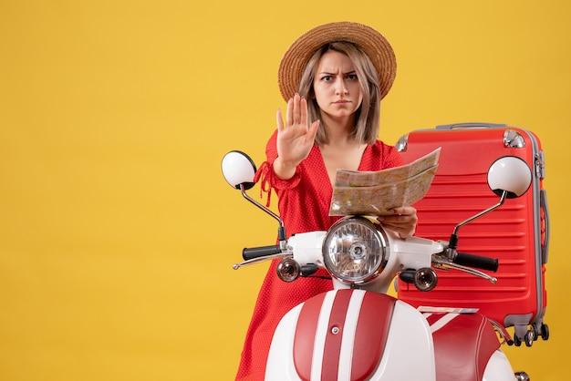 Vue de face jeune femme en robe rouge tenant une carte faisant un panneau d'arrêt près d'un cyclomoteur