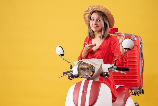 Vue de face jeune femme en robe rouge tenant une carte de réduction sur un cyclomoteur