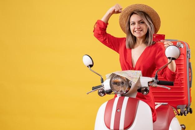 Vue de face jeune femme en robe rouge tenant une carte de réduction près d'un cyclomoteur