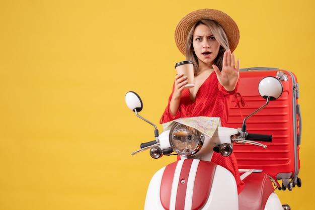 Vue de face jeune femme en robe rouge tenant une tasse de café gesticulant un panneau d'arrêt près d'un cyclomoteur