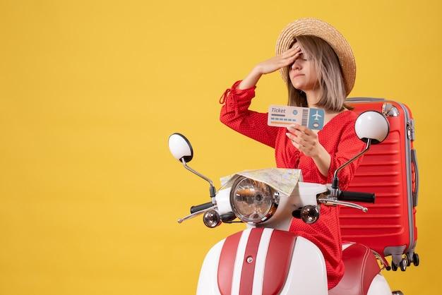 Vue de face jeune femme en robe rouge avec ticket tenant sa tête sur un cyclomoteur
