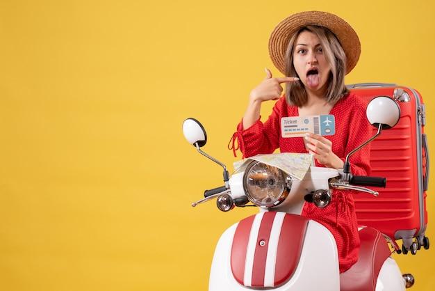 Vue de face jeune femme en robe rouge tirant la langue tenant un ticket sur un cyclomoteur