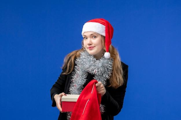 Vue de face d'une jeune femme avec un sac cadeau rouge sur un mur bleu