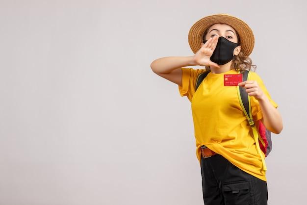 Vue de face jeune femme avec sac à dos brandissant une carte appelant quelqu'un