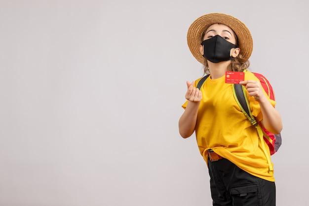 Vue de face jeune femme avec sac à dos brandissant une carte faisant de l'argent signe