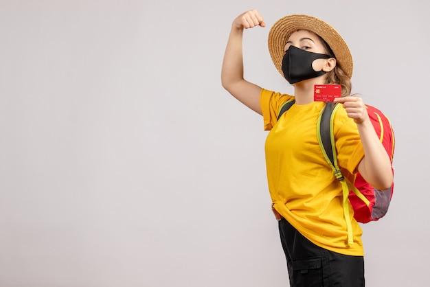 Vue de face jeune femme avec sac à dos brandissant une carte montrant le muscle du bras