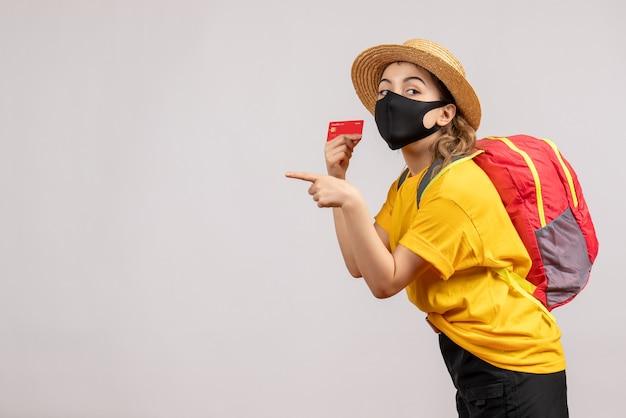 Vue de face jeune femme avec sac à dos brandissant une carte pointant vers la gauche
