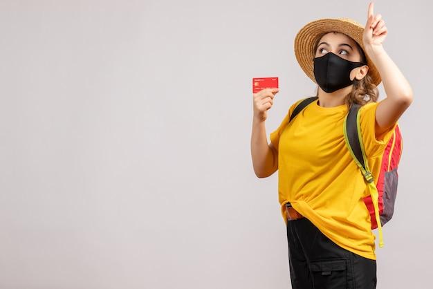 Vue de face jeune femme avec sac à dos brandissant le doigt pointé vers le haut