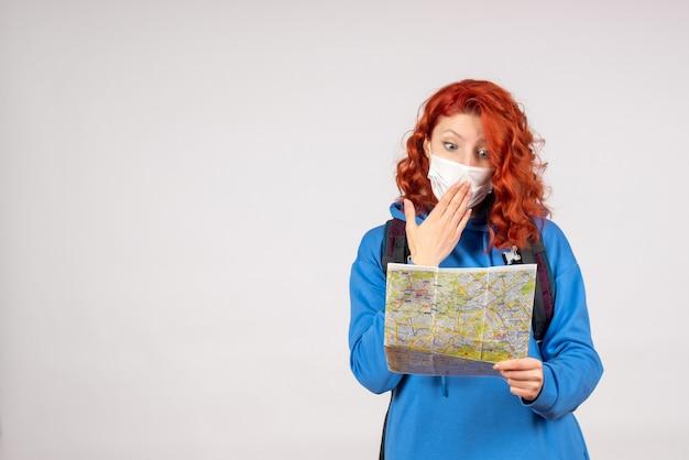 Vue de face de la jeune femme avec sac à dos et carte en masque sur mur blanc