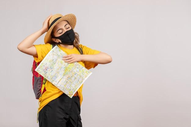 Vue de face jeune femme avec sac à dos tenant une carte fermant les yeux