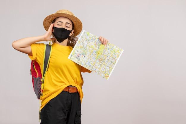 Vue de face jeune femme avec sac à dos tenant la carte en fermant les yeux