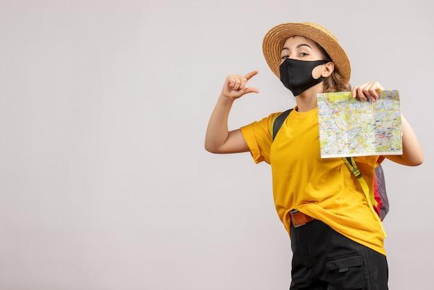 Vue de face jeune femme avec sac à dos tenant une carte montrant la taille avec les doigts