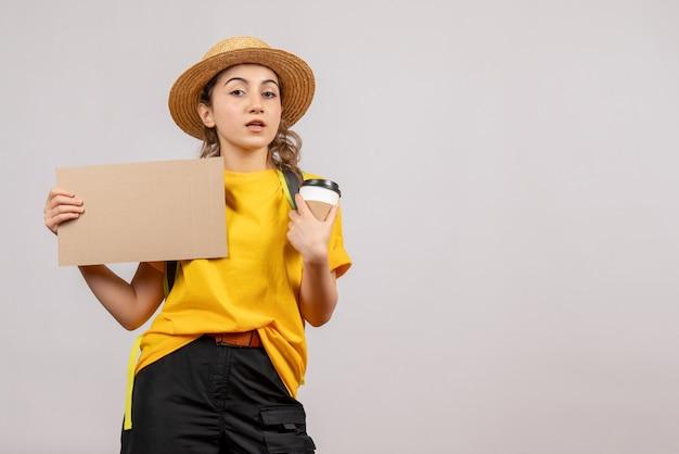 Vue de face jeune femme avec sac à dos tenant du carton et du café