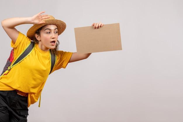 Vue de face jeune femme avec sac à dos tenant du carton