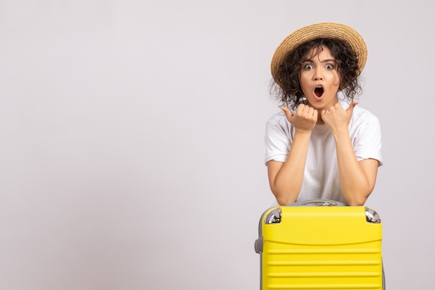 Vue de face jeune femme avec sac jaune se préparant au voyage sur fond blanc vol reste voyage vacances touristiques couleur avion soleil