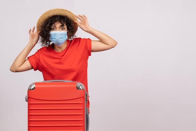 Vue de face jeune femme avec sac en masque sur fond blanc couleur covid- voyage vacances touristiques soleil virus voyage