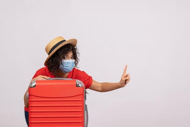 Vue de face jeune femme avec sac en masque sur fond blanc couleur covid- voyage vacances touristiques voyage pandémie du virus du soleil
