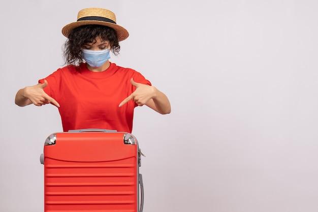 Vue de face jeune femme avec sac en masque sur fond blanc covid- virus pandémique voyage touriste couleur soleil