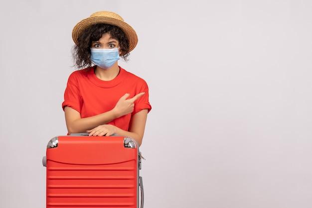 Vue de face jeune femme avec sac en masque sur fond blanc virus de couleur covid- voyage de vacances pandémique touriste du soleil
