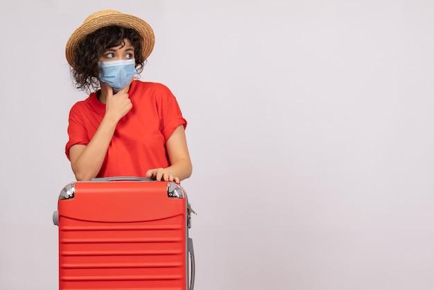 Vue de face jeune femme avec sac en masque sur fond blanc virus covid- voyage de couleur de vacances de pandémie de soleil touristique
