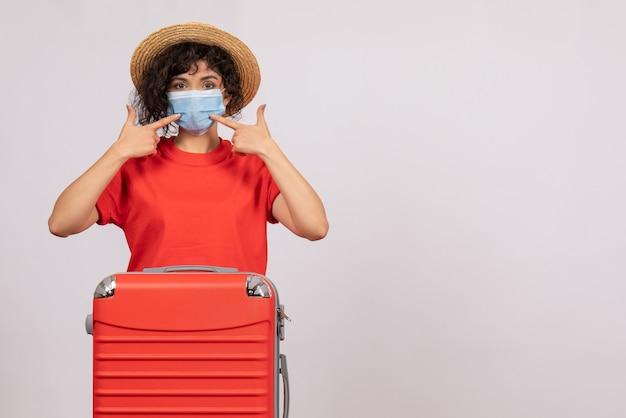 Vue de face jeune femme avec sac en masque sur fond blanc virus covid- voyage de couleur vacances soleil touristique