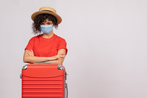 Vue de face jeune femme avec sac en masque sur fond blanc virus covid- voyage de couleurs de vacances de pandémie de soleil touristique