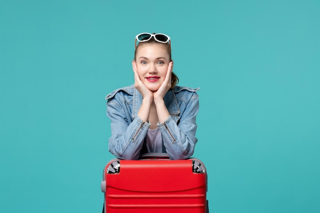 Vue de face jeune femme avec sac de préparation pour les vacances sur l'espace bleu