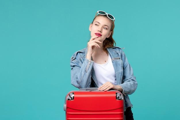 Vue de face jeune femme avec sac de préparation pour les vacances et de réflexion sur l'espace bleu