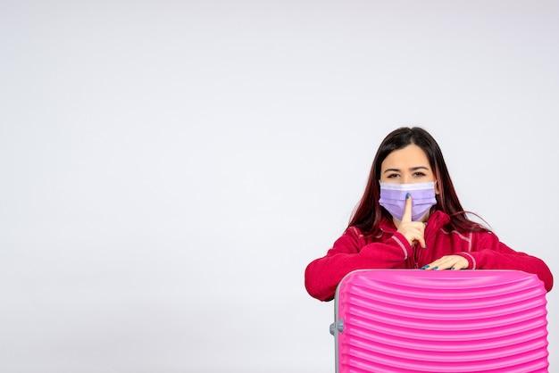 Vue de face jeune femme avec sac rose en masque sur mur blanc vacances virus pandémique covid- couleur voyage femme
