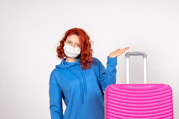 Vue de face de la jeune femme avec sac rose en masque sur mur blanc