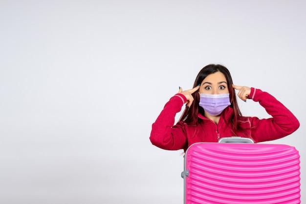 Vue de face jeune femme avec sac rose en masque stérile sur mur blanc couleur virus femme covid- vacances voyage pandémique