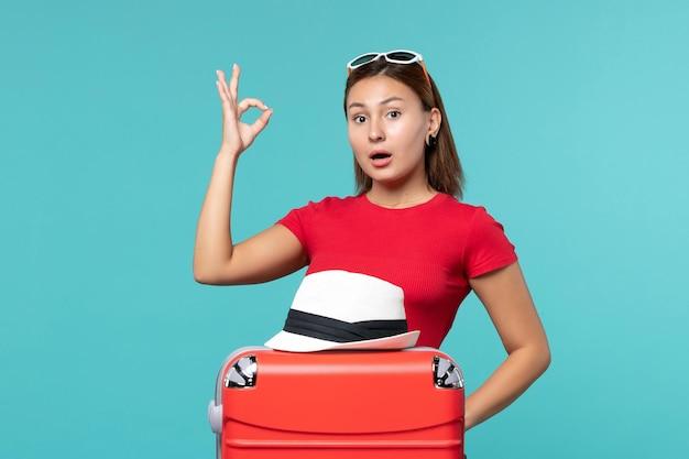 Vue de face jeune femme avec sac rouge et chapeau sur bureau bleu
