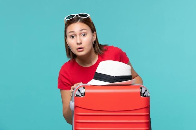 Vue de face jeune femme avec sac rouge et chapeau dessus sur un bureau bleu
