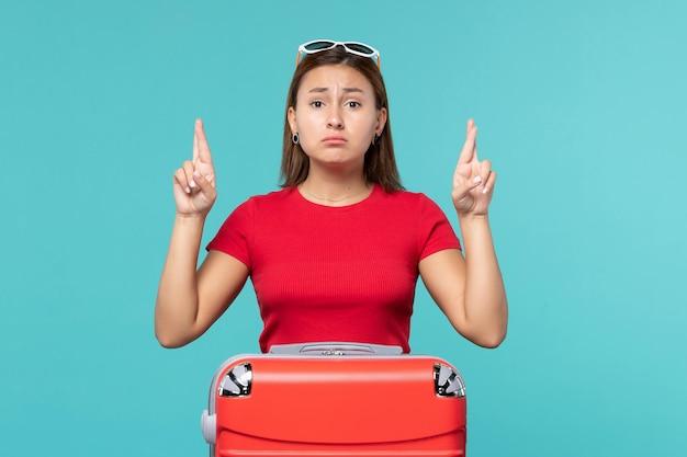 Vue de face jeune femme avec sac rouge croisant ses doigts sur l'espace bleu