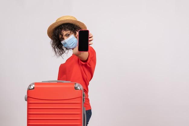 Vue de face jeune femme avec sac rouge dans un masque tenant un téléphone sur fond blanc soleil covid voyage pandémique couleur du virus touristique