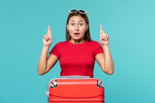 Vue de face jeune femme avec sac rouge sur l'espace bleu clair