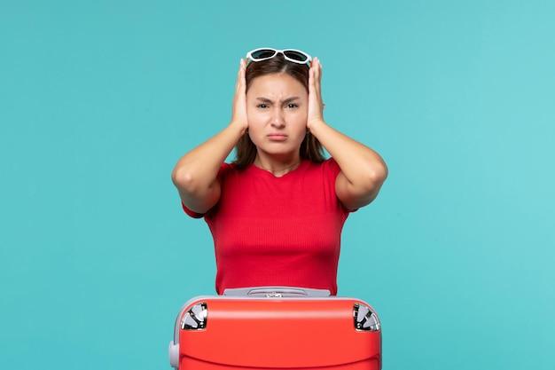 Vue de face jeune femme avec sac rouge sur l'espace bleu
