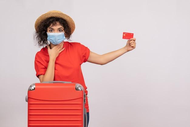 Vue de face jeune femme avec sac rouge en masque tenant une carte bancaire sur fond blanc soleil covid pandémie voyage de vacances couleur touristique
