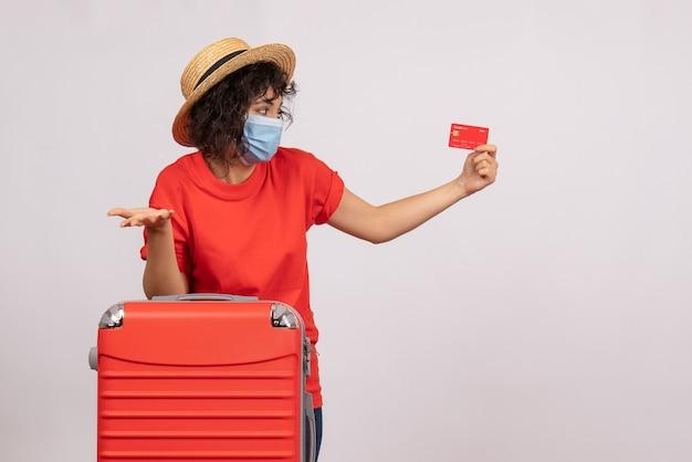 Vue de face jeune femme avec sac rouge en masque tenant une carte bancaire sur fond blanc soleil covid pandémie voyage vacances couleurs touristiques