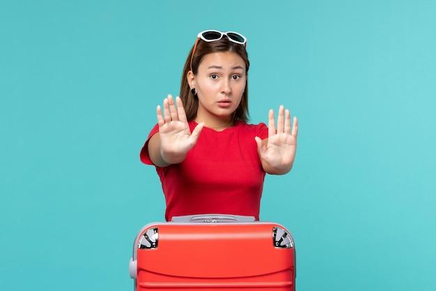 Vue de face jeune femme avec sac rouge posant sur l'espace bleu