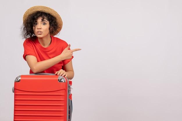 Vue de face jeune femme avec sac rouge se préparant au voyage sur fond blanc avion reste vacances couleur soleil vol touristique