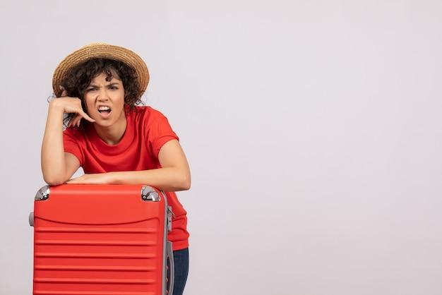 Vue de face jeune femme avec sac rouge se préparant au voyage sur fond blanc avion reste vacances soleil vol voyage voyage