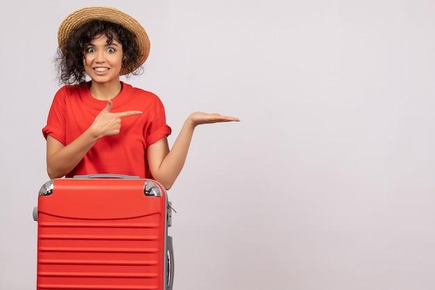 Vue de face jeune femme avec sac rouge se préparant au voyage sur fond blanc couleur avion reste vacances soleil vol touristique