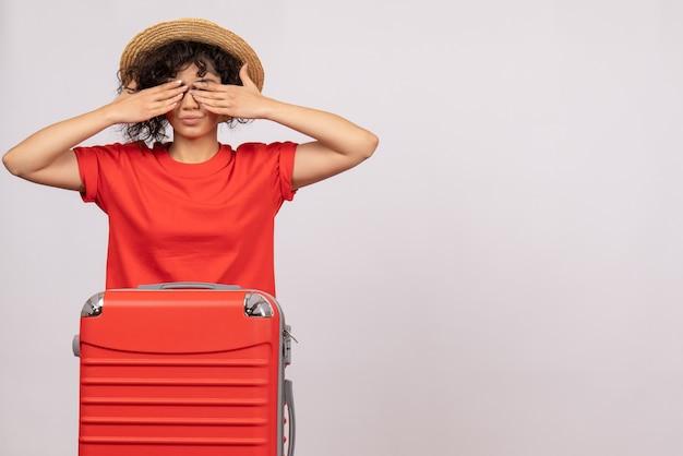 Vue de face jeune femme avec sac rouge se préparant au voyage sur fond blanc couleur avion reste vacances soleil vol voyage