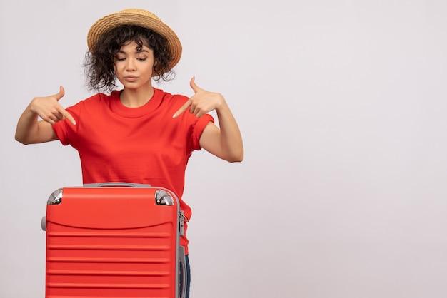 Vue de face jeune femme avec sac rouge se préparant au voyage sur fond blanc couleur avion reste vacances soleil voyage touristique